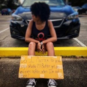 """Dr. Jordan sits on a yellow parking bumper, looking off into the distance towards the left. Perched before her feet and legs is a cardboard sign reading """"Do I matter to your yoga studio?! Better yet, do you even notice when I'm not there?"""""""