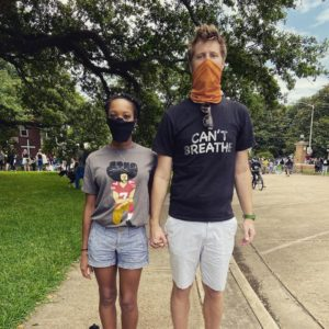 """Dr. Valin Jordan and Dr. Matthew Green stand side-by-side, hands clasped. She is wearing a grey t-shirt with a cartoonized image of Colin Kaepernick kneeling and shorts. He is wearing a black t-shirt with the words """"I can't Breathe"""" and shorts."""