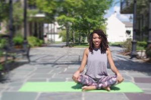 Dr. Valin Jordan sits cross legged on a green yoga mat with her hands at her knees.